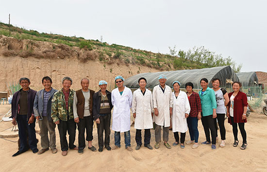 6月2日,山西省吕梁市临县兔坂镇砖瓦村村主任武雪峰(左七)与部分鸡场入股村民的合影。