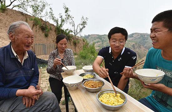 6月2日,山西省吕梁市临县兔坂镇砖瓦村村主任武雪峰(右二)和鸡场工作人员吃午饭。
